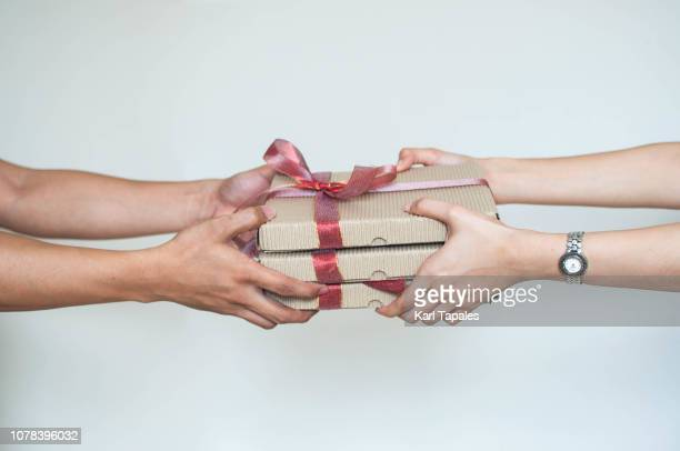 close-up of two persons sharing gifts - donate icon stock photos and pictures