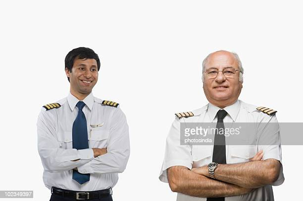 Close-up of two pilots smiling with their arms crossed