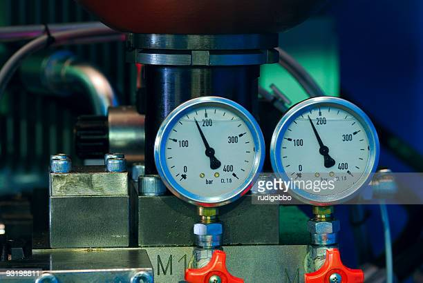 Close-up of two pressure gauges with red valves