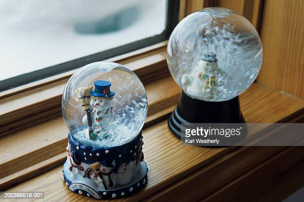 Close-up of two snow globes on window ledge, close-up