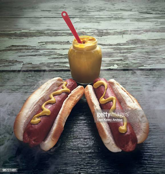Closeup of two steaming hot dogs on a wooden table with a jar of mustard 1980