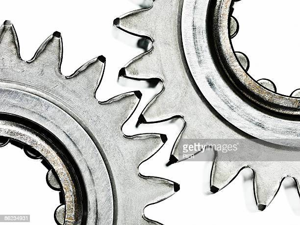 Close-up of two steel gears / cogs linked on white