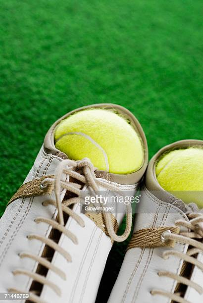 Close-up of two tennis balls in a pair of sports shoes