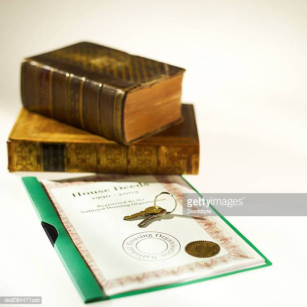 close-up of two textbooks with house deeds and keys beside it - deed stock photos and pictures