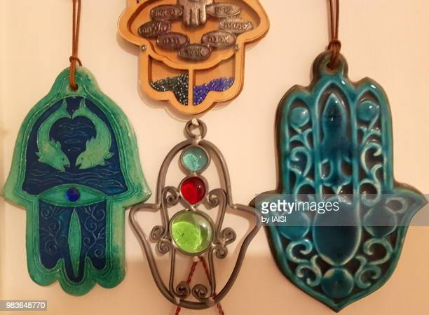 close-up of two turquoise-colored hamsas for house protection from the evil eye - hand of fatima stock photos and pictures