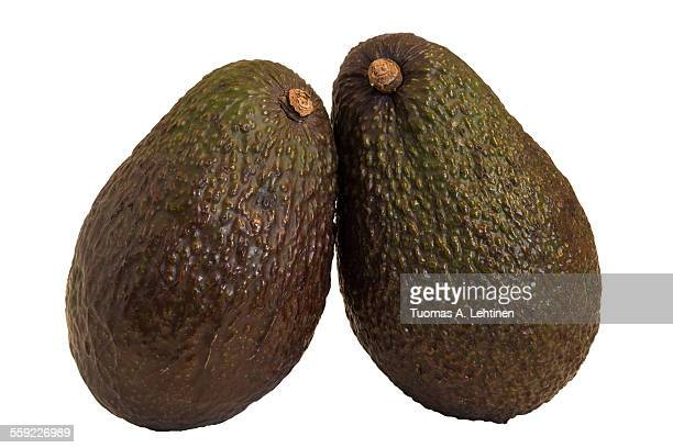 Close-up of two whole avocados