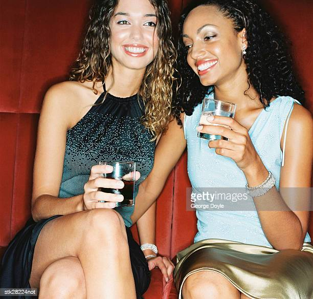 close-up of two women sitting in a club with drinks in hand - only mid adult women stock pictures, royalty-free photos & images