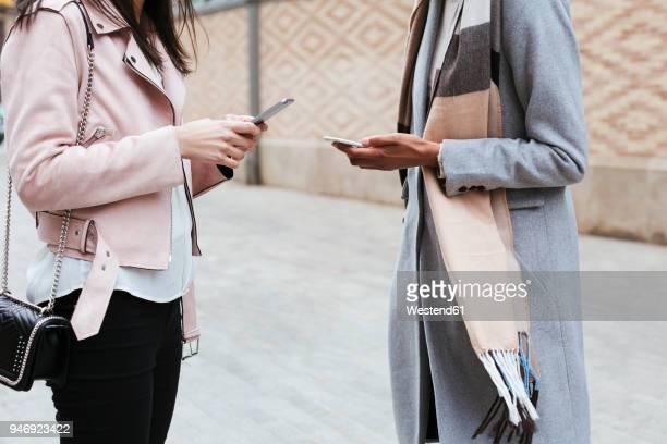 close-up of two women using cell phones in the city - mensajería instantánea fotografías e imágenes de stock