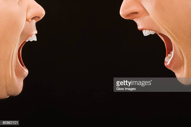 close-up of two young men shouting at each other - rabbia emozione negativa foto e immagini stock