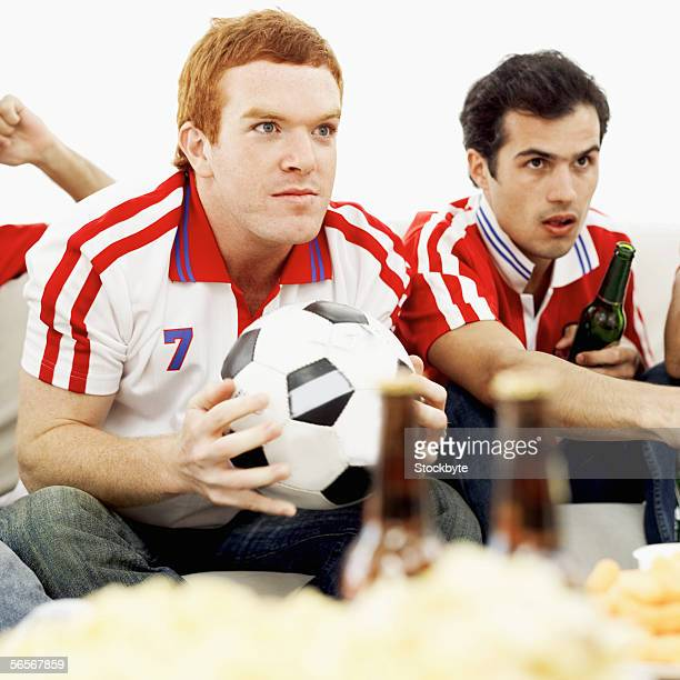 close-up of two young men wearing soccer jerseys