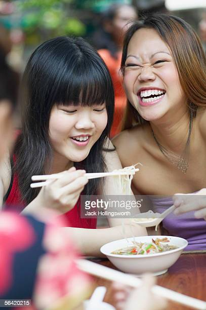 Close-up of two young women eating noodles with chopsticks