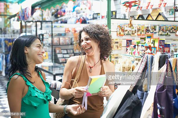 close-up of two young women smiling in a gift store - ギフトショップ ストックフォトと画像