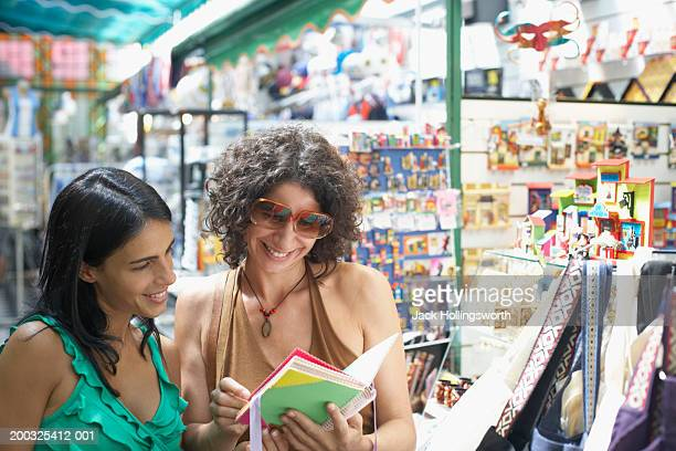 close-up of two young women standing in a gift store - ギフトショップ ストックフォトと画像