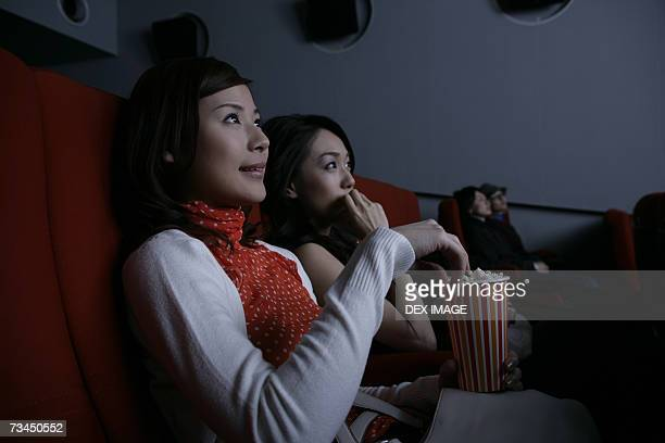 Close-up of two young women watching a movie in a movie theater