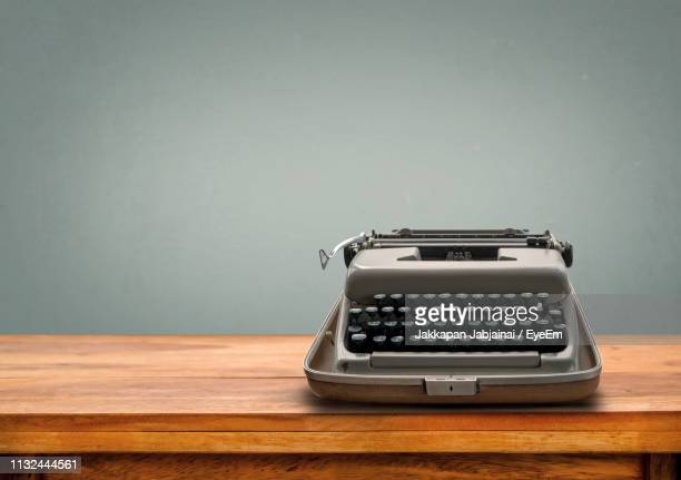 close-up of typewriter on wooden table against gray wall - タイプライター ストックフォトと画像