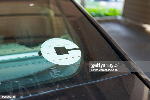 Closeup of Uber logo on the back of a crowdsourced taxi or ridesharing car parked in a suburban setting Dublin California May 7 2018