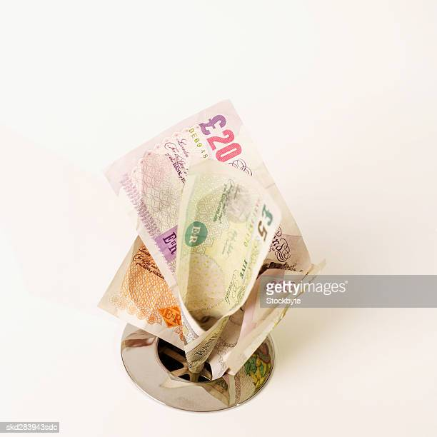 Close-up of U.K.. pound notes going down the drain