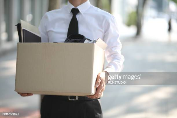 close-up of unemployed businessperson carrying cardboard box - downsizing unemployment stock pictures, royalty-free photos & images