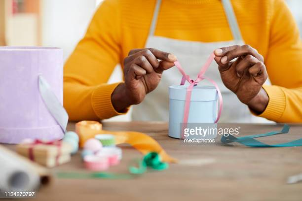 Close-up of unrecognizable black man tying ribbon on small gift box in workshop, gift wrapping service
