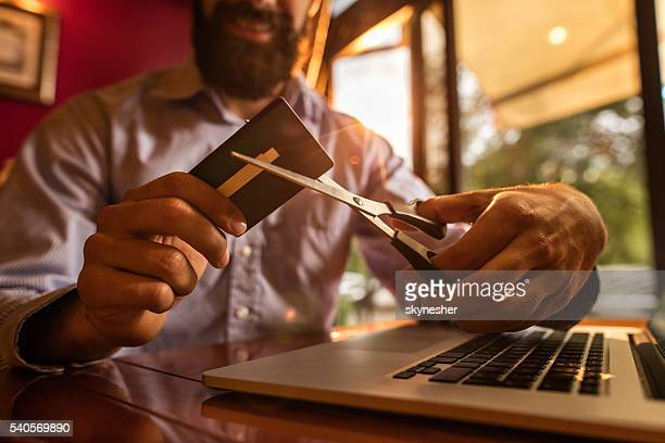 Close-up of unrecognizable businessman cutting credit card with scissors.