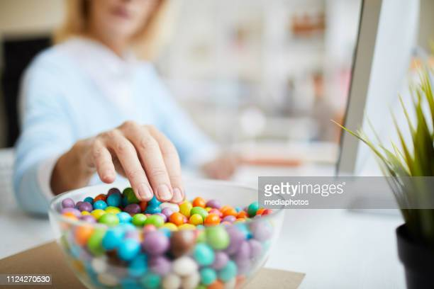 close-up of unrecognizable businesswoman sitting at table and eating sweet beans while working in office - sweet food stock pictures, royalty-free photos & images