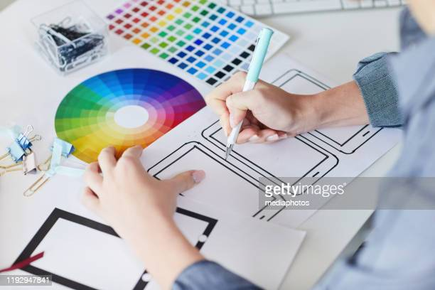 close-up of unrecognizable designer sitting at desk with papers and drawing interface design for digital devices - design professional stock pictures, royalty-free photos & images