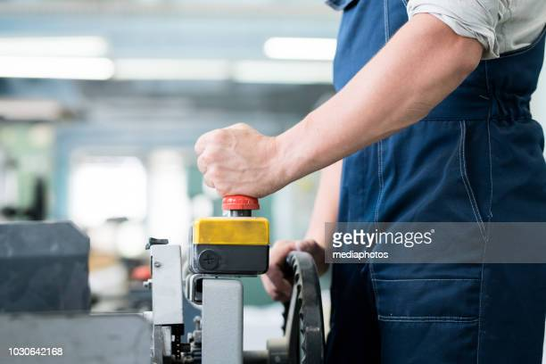 Close-up of unrecognizable factory worker in overall operating industrial machine with remote control, he pushing ed button while launching conveyor