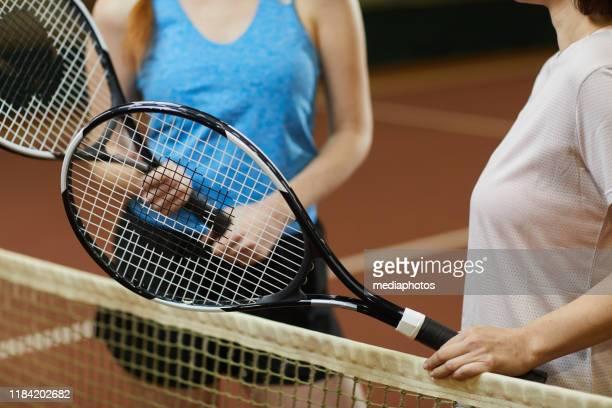 ゲームについて話し合いながら、ネットに立ち、個人的なラケットを保持している認識できない女子テニス選手のクローズアップ - テニスラケット ストックフォトと画像