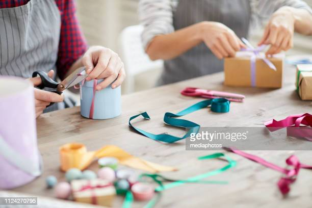 Close-up of unrecognizable skilled craftspeople sitting at table with colorful ribbons and tying it on boxes