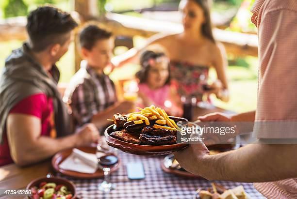 Primer plano de irreconocible camarero donde se sirve comida para su familia en el restaurante.