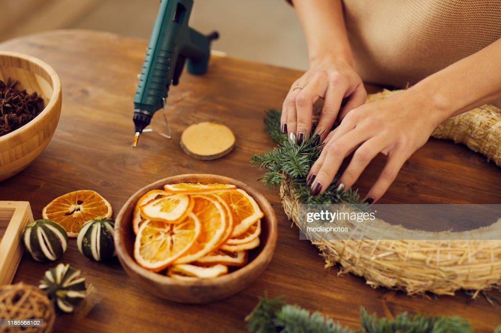 Close-up van onherkenbaar vrouw met manicure staande op houten tafel in workshop en het gebruik van hete lijm tijdens het bevestigen van Fir Tree twijgen aan krans basis : Stockfoto