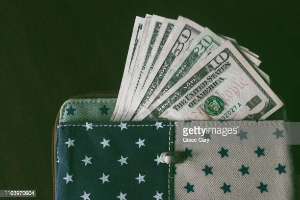 close-up of us currency sticking out of star-patterned wallet - 10 dollar schein us dollar geldschein stock-fotos und bilder