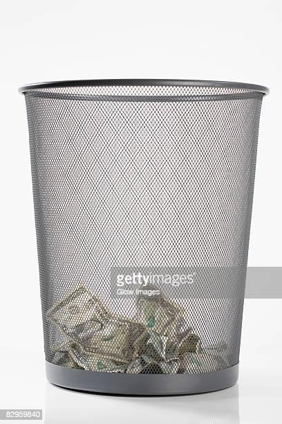 Close-up of US dollar bills in a garbage bin