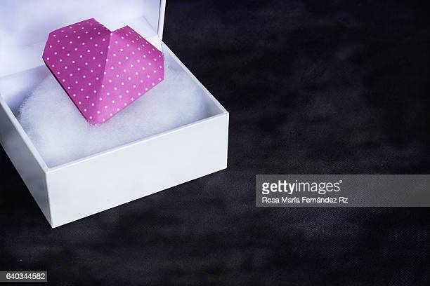 Close-up of Valentine's heart in a open gift box. Origami Heart done with pink polka dot paper. Subject captured against soft window lighting over abstract background with copy space