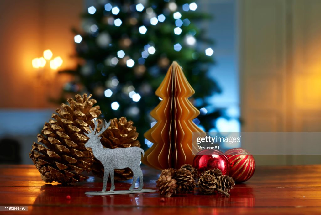 Close-up of various decorations on wooden table with illuminated Christmas tree in background at home : Stockfoto