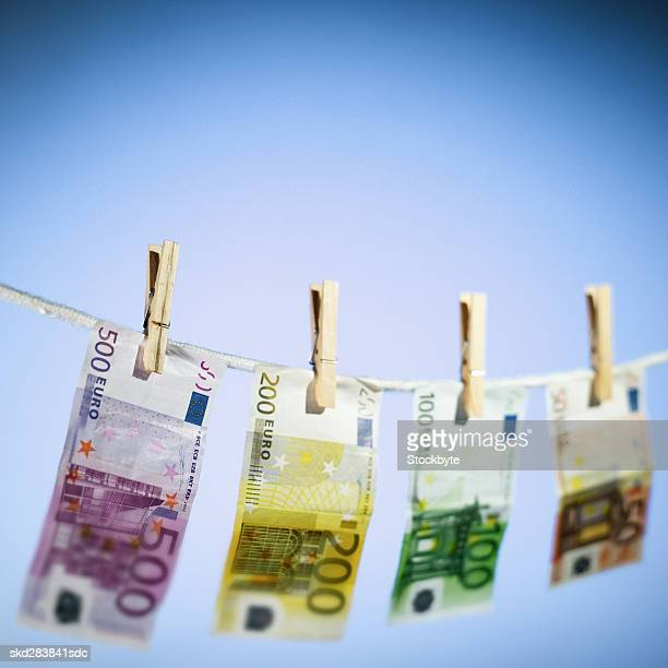 Close-up of various euro notes hanging on clothesline
