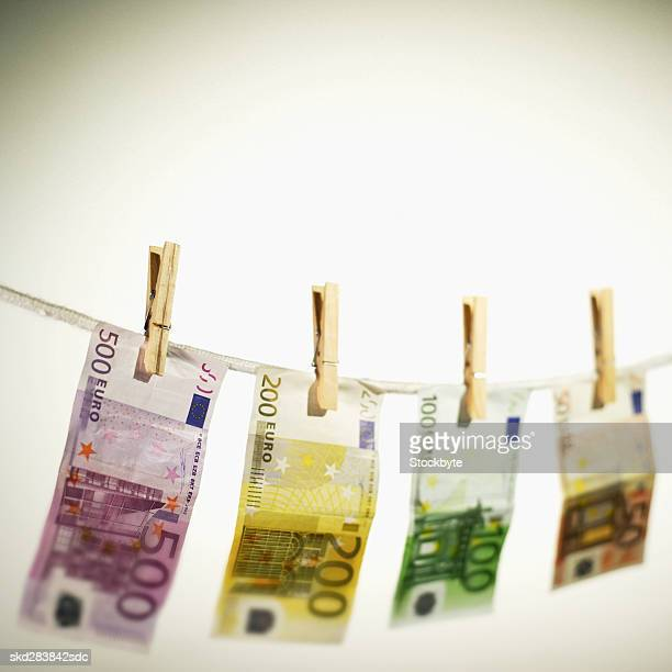 close-up of various euro notes hanging on clothesline - money laundering stock photos and pictures