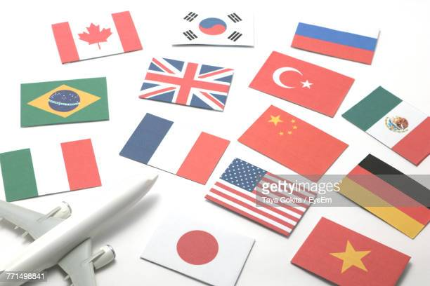 Close-Up Of Various Flags And Model Airplane Over White Background