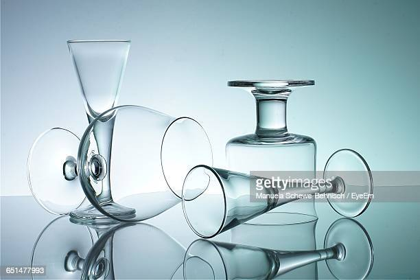 Close-Up Of Various Glasses Against Colored Background