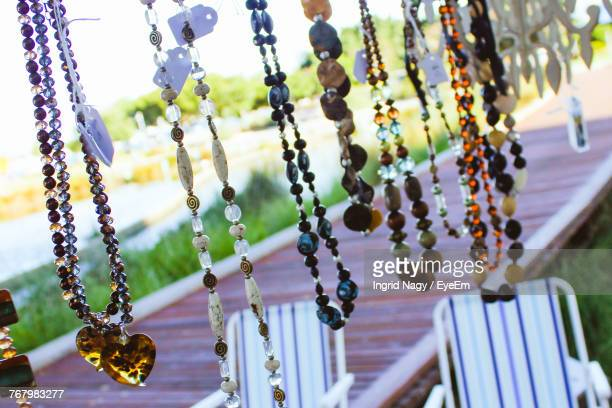 Close-Up Of Various Necklaces Hanging Against Boardwalk