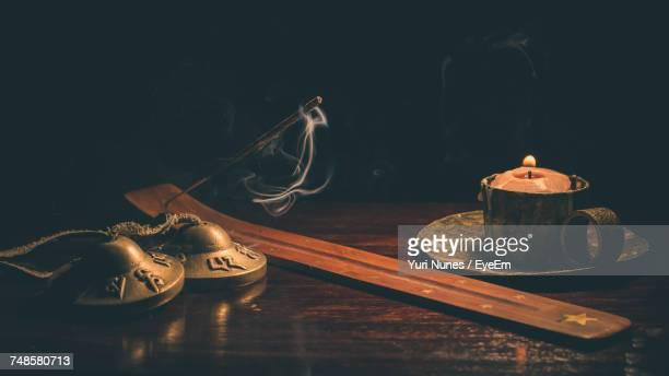 close-up of various religious equipment on wooden table in darkroom - incense stock photos and pictures