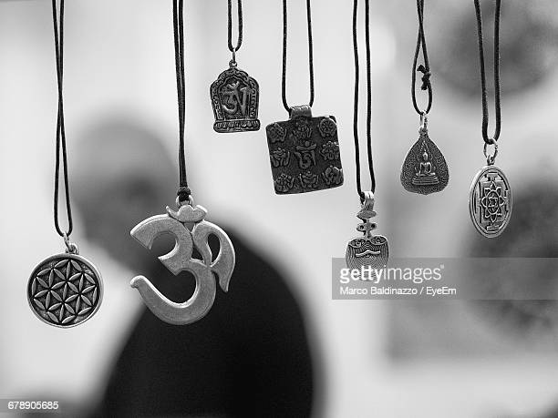 Close-up Of Various Religious Necklaces Hanging For Sale At Market