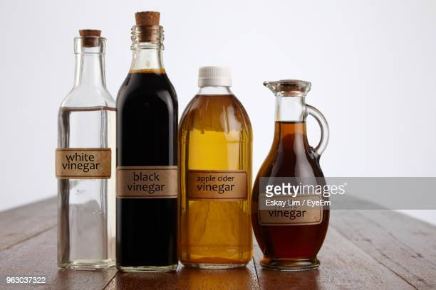 close-up of various vinegars on table against white background - condiment stock pictures, royalty-free photos & images