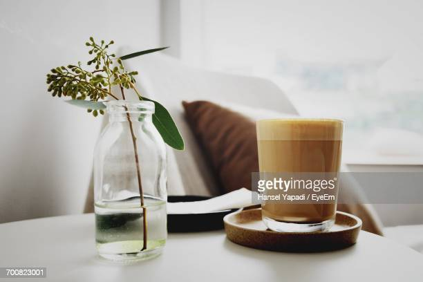 Close-Up Of Vase And A Cappuccino Glas On Table At Home