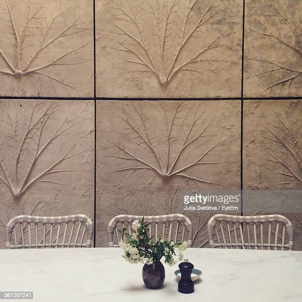 Close-Up Of Vase On Table Against The Wall