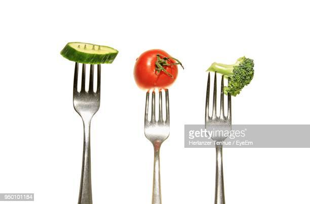 close-up of vegetables in forks against white background - forchetta foto e immagini stock