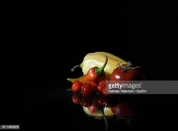 close-up of vegetables reflecting on glass table against black background - nathalie pellenkoft stock pictures, royalty-free photos & images