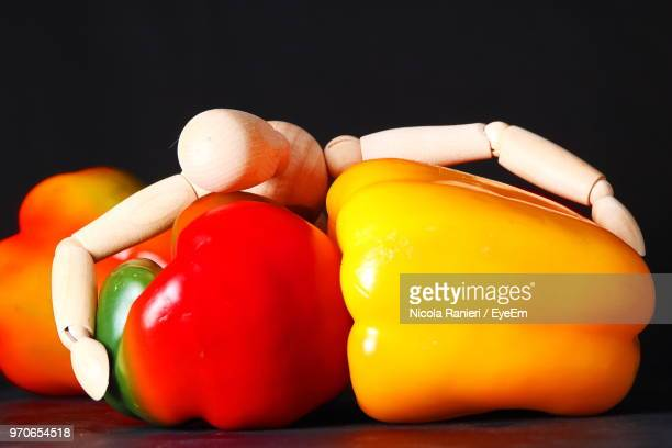 Close-Up Of Vegetables With Figurine On Table Against Black Background
