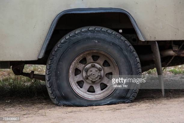 close-up of vehicle with flat tire on field - puncturing stock pictures, royalty-free photos & images
