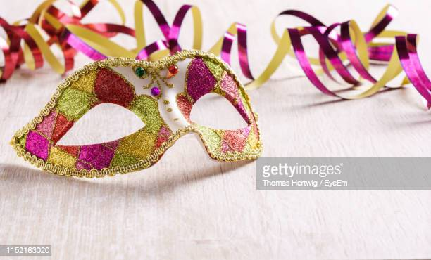 close-up of venetian mask by ribbon on table - maschere carnevale foto e immagini stock